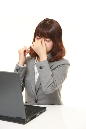 eyestrain: young Japanese businesswoman suffers from Asthenopia Stock Photo