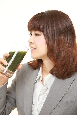 office women: Japanese businesswoman with green vegetable juice
