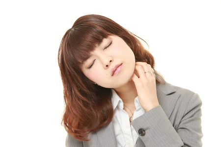 businesswoman suit: Japanese businesswoman scratching her neck Stock Photo