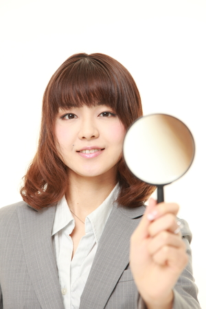 businesswoman suit: Japanese businesswoman with a magnifying glass