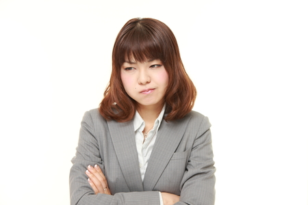 scowl: young Japanese businesswoman in a bad mood Stock Photo