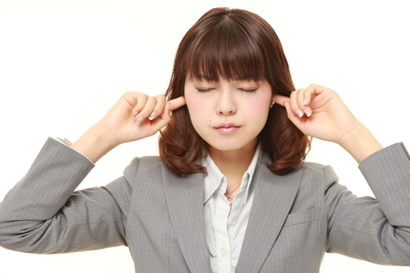 suffers: Young Japanese businesswoman suffers from noise Stock Photo