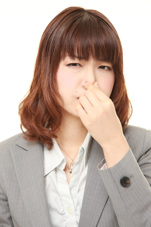 businesswoman suit: Japanese businesswoman holding her nose because of a bad smell