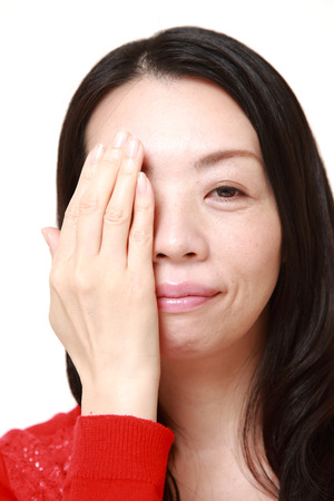 one eye: Japanese woman covering one eye with her hand Stock Photo