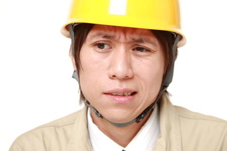 perplexed: perplexed Japanese construction worker