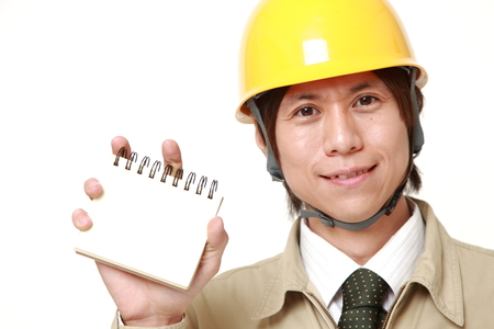 Japanese construction worker holding blank notebook