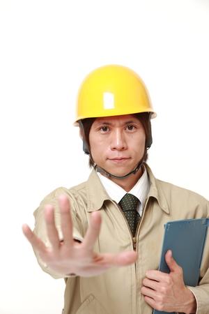 停止ジェスチャーを作る若い建設労働者 写真素材
