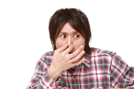 bad smell: Japanese man holding his nose because of a bad smell
