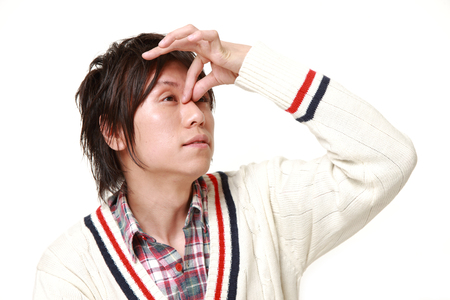 eyestrain: young Japanese man suffers from Asthenopia Stock Photo