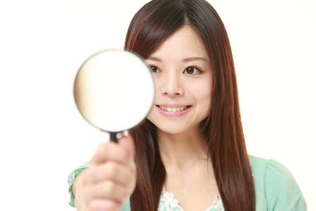 虫眼鏡で日本人女性 写真素材