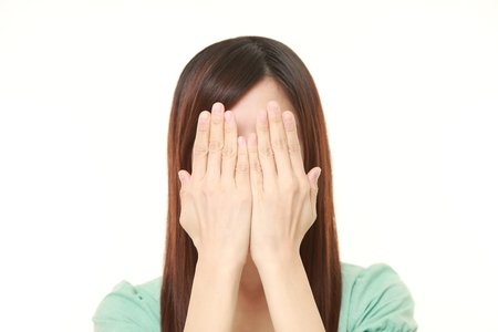 one eye: woman covering her face with hands Stock Photo