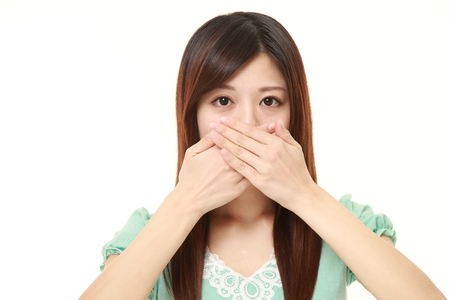 Japanese woman making the speak no evil gesture Imagens