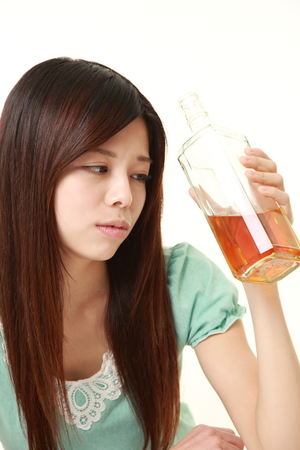 drunkenness: young Japanese woman drinking straight from a bottle