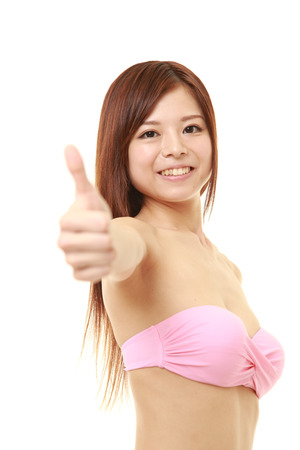pink bikini: young Japanese woman in a pink bikini with thumbs up gesture Stock Photo