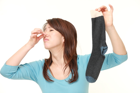 Japanese woman holding her nose because of a bad smell of a socks