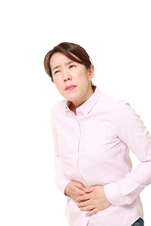 suffers: Japanese woman suffers from stomachache Stock Photo