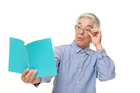 farsighted: senior Japanese man with presbyopia
