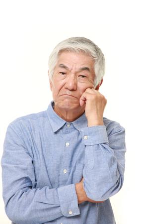worries: senior Japanese man worries about something Stock Photo