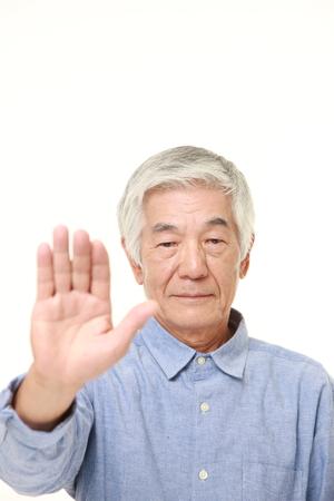 停止ジェスチャーを作る日本の年配の男性 写真素材