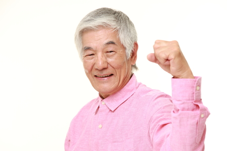 old man happy: senior Japanese man in a victory pose
