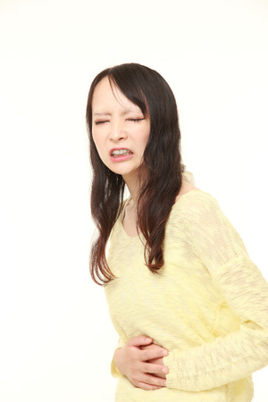 defecation: young Japanese woman suffers from stomachache Stock Photo