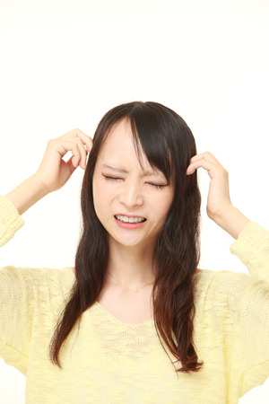 eyestrain: young Japanese woman suffers from headache