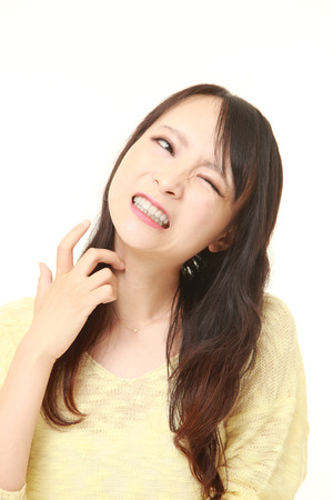 scratching: Japanese woman scratching her neck Stock Photo