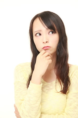 worries: young Japanese woman worries about something
