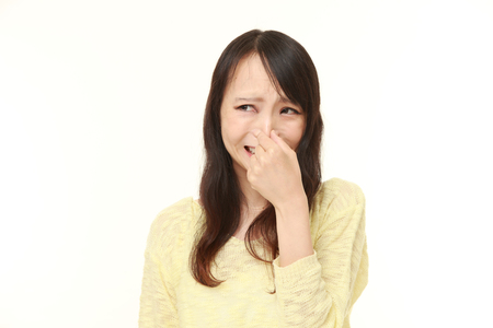 bad hair: Japanese woman holding her nose because of a bad smell Stock Photo