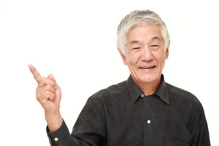 senior men: senior Japanese man presenting and showing something