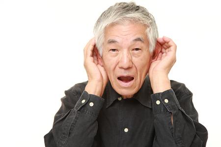 hombre japonés mayor con la mano detrás de la oreja escuchando de cerca Foto de archivo