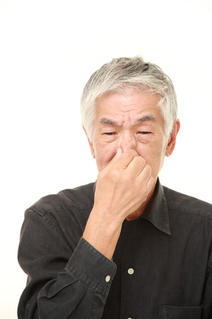 bad smell: senior Japanese man holding his nose because of a bad smell Stock Photo