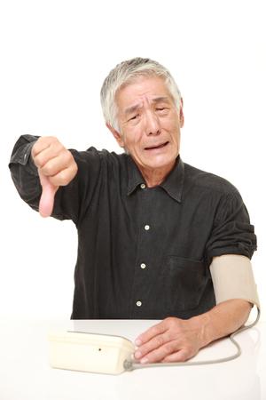 blood pressure monitor: senior Japanese man checking his blood pressure shocked