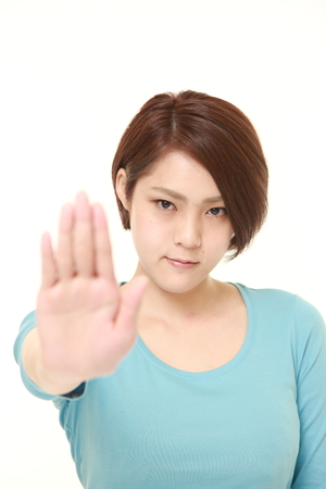 stop: young Japanese woman making stop gesture