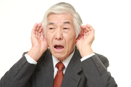 closely: senior Japanese businessman with hand behind ear listening closely