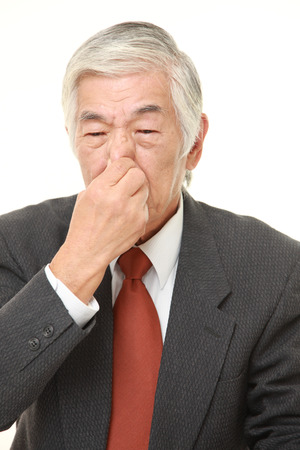 bad smell: senior Japanese businessman holding his nose because of a bad smell Stock Photo