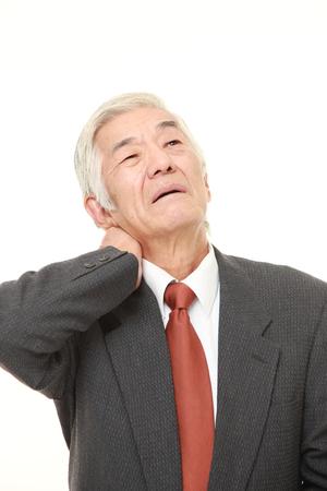 mature business man: senior Japanese businessman suffers from neck ache Stock Photo