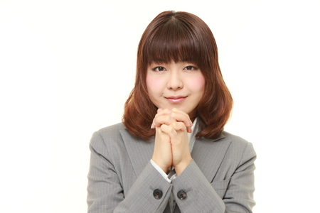 remorse: young Japanese businesswoman folding her hands in prayer