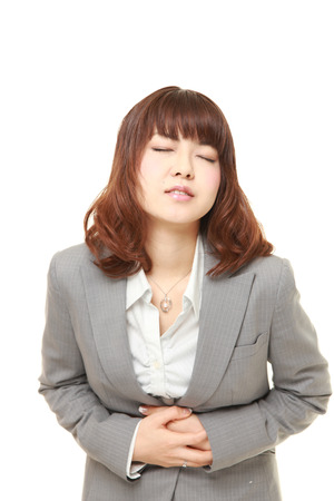 suffers: young Japanese businesswoman suffers from stomachache