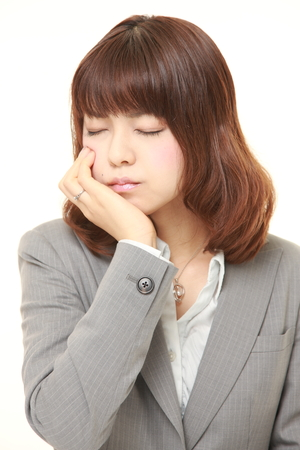 suffers: young Japanese businesswoman suffers from toothache Stock Photo