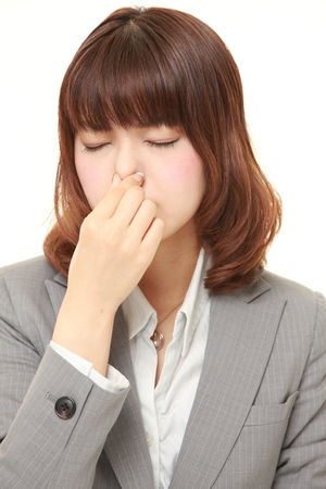 bad smell: Japanese businesswoman holding her nose because of a bad smell
