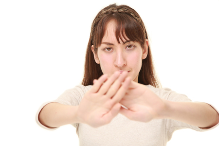 rejecting: young woman making stop gesture