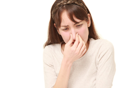 woman holding her nose because of a bad smell