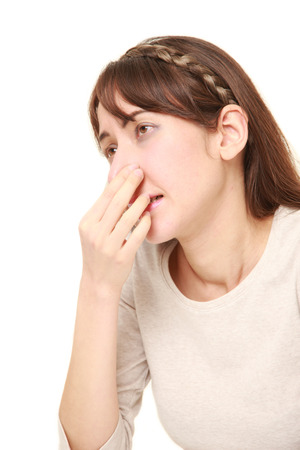 bad smell: woman holding her nose because of a bad smell