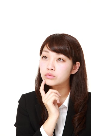 thinks: young Japanese businesswoman thinks about something Stock Photo