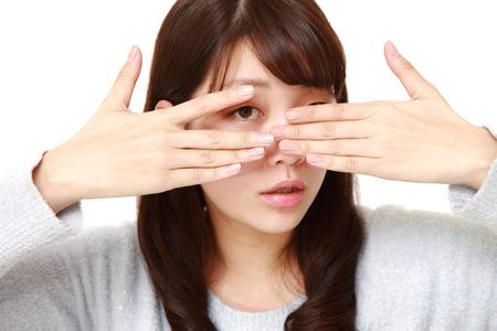 hands covering face: woman covering her face with hands peeping at the camera through her fingers Stock Photo