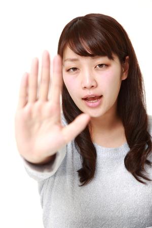 停止ジェスチャーを作る若い日本の実業家