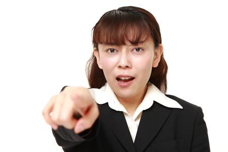 denunciation: middle aged Asian businesswoman scolding Stock Photo