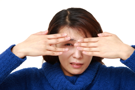 unattractive: woman covering her face with hands peeping at the camera through her fingers Stock Photo