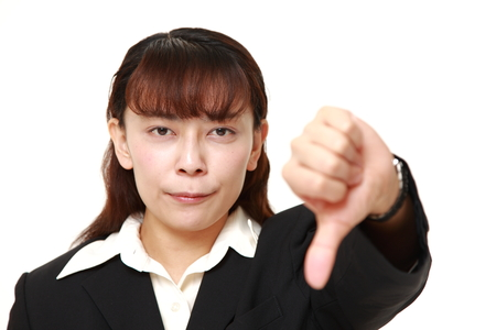 Asian businesswoman with thumbs down gesture Stock Photo